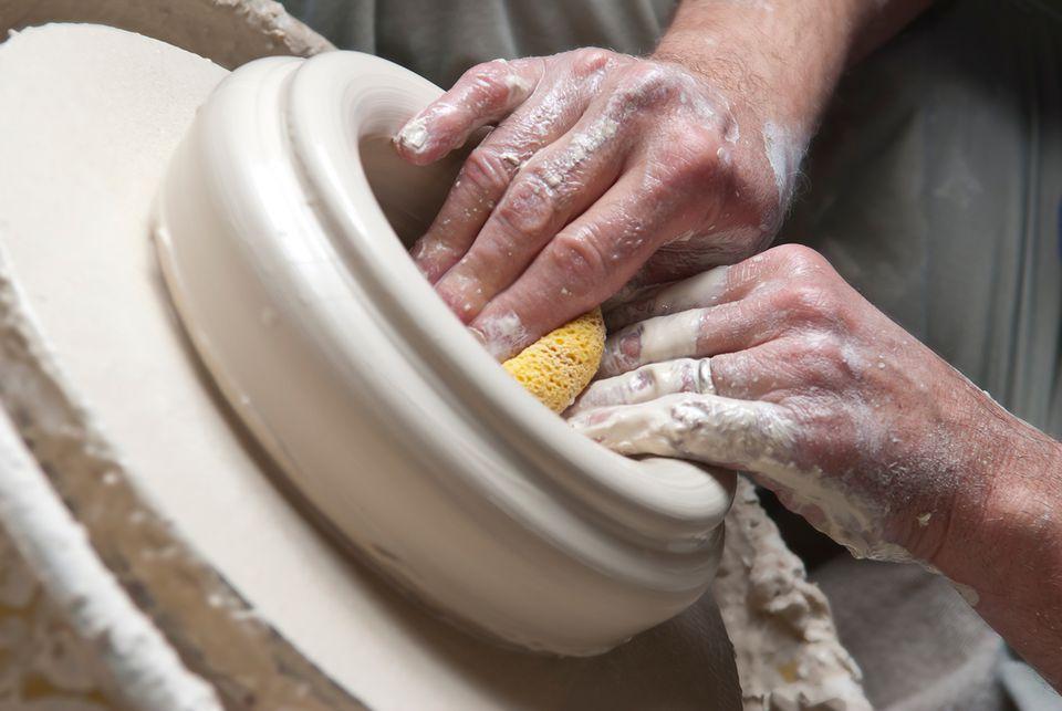 Potter uses sponge to shape bowl on pottery wheel.