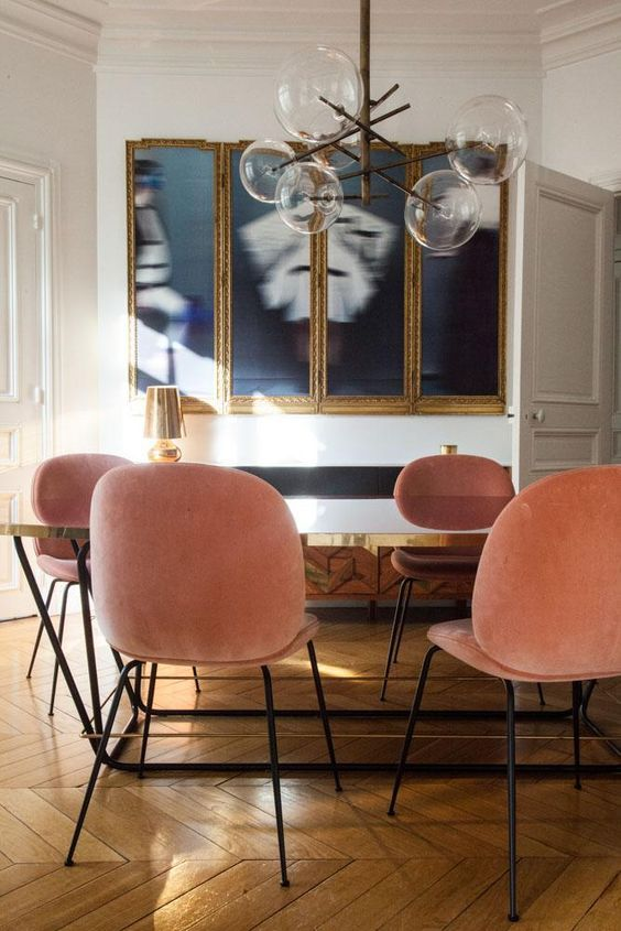 Dining room with blue art and pink chairs