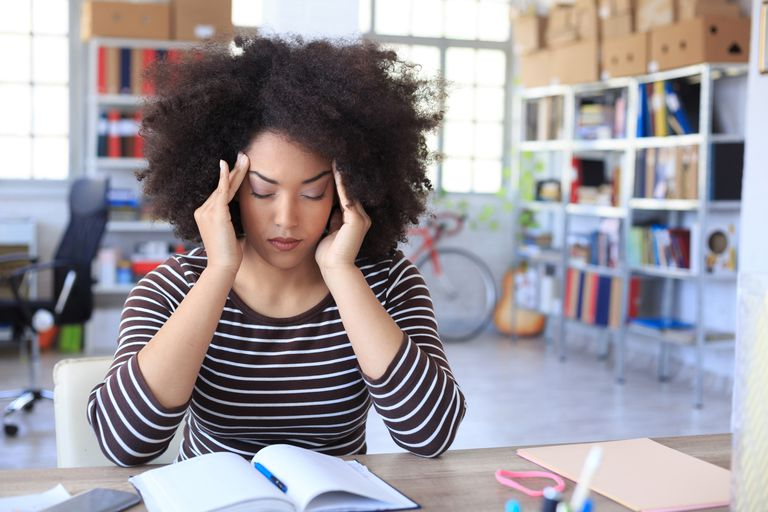 Young woman has a headache at the office