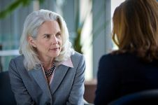older businesswoman speaks with younger business woman