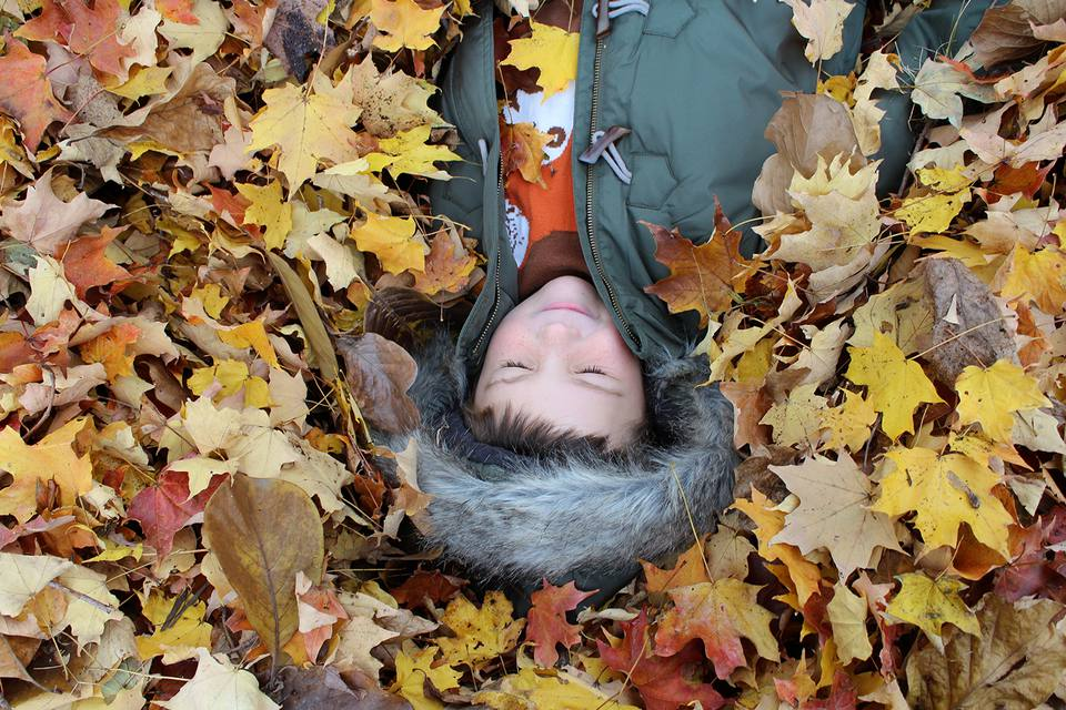 Little boy laying on his back in a pile of colorful autumn maple leaves.