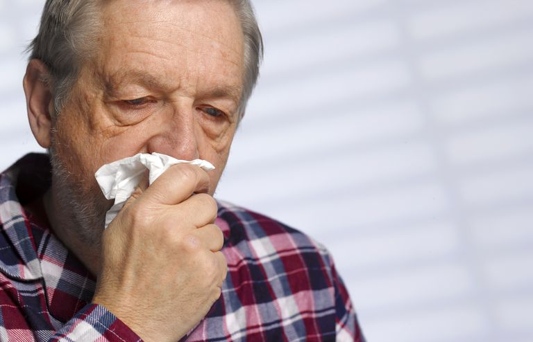 Excessive mucus production. Senior man with a cold blowing his nose
