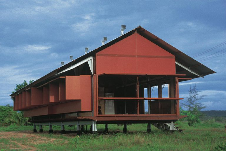 red-colored, open-aired gabled-roofed structure sitting above the ground on a series of low posts