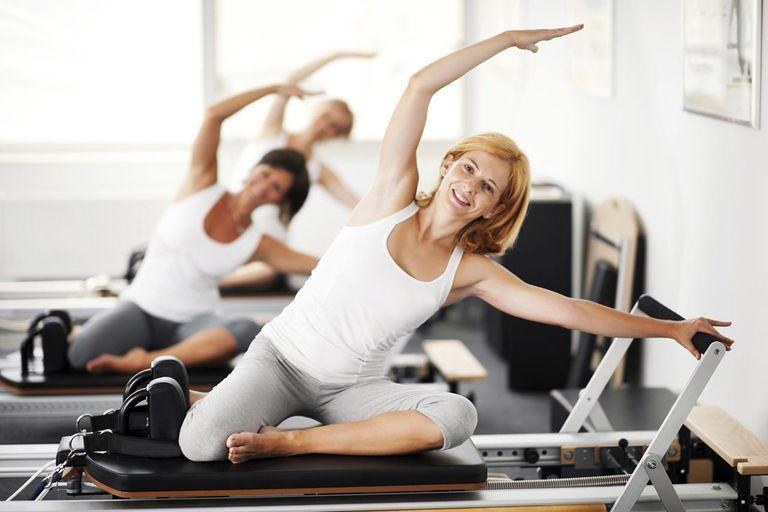 Three women exercising on a Pilates machine.