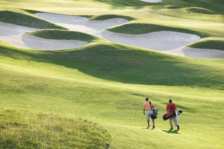 Two senior golfers walking down the fairway