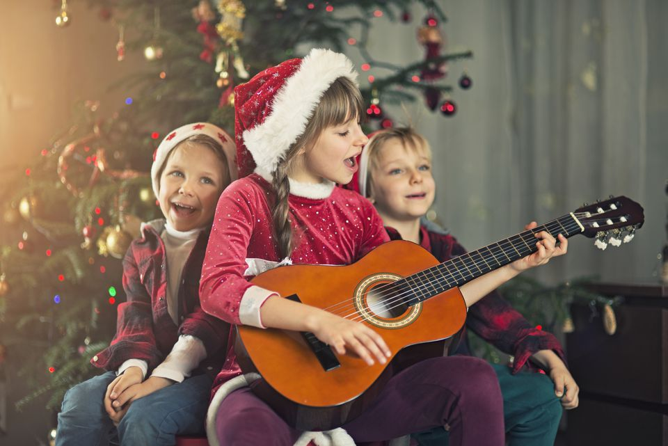 Kids singing carols near the christmas tree