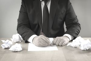 Man writing letter and crumpled papers
