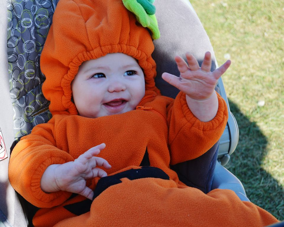 High Angle View Of Baby In Pumpkin Costume Relaxing On Carriage
