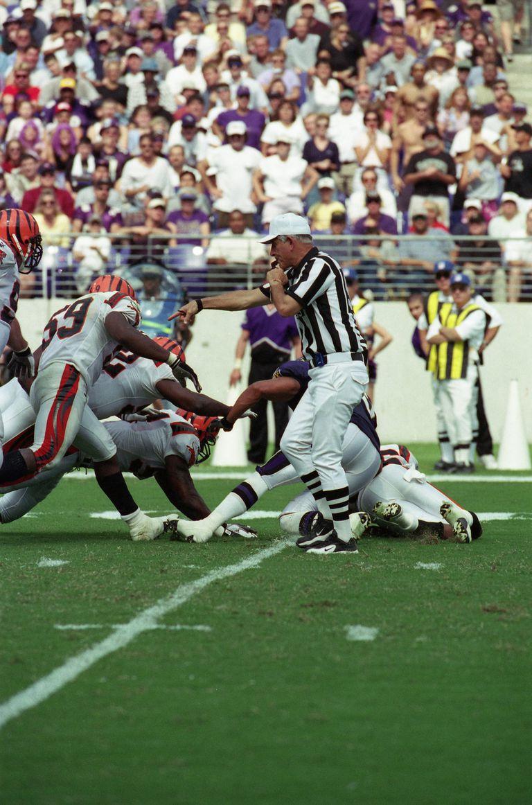 Referee Bob McElwee #95 calls a clipping penalty on Fullback Obafemi Ayanbadejo #30 of the Baltimore Ravens for hitting the ball carrier of the Cincinnati Bengals in the back during an NFL football game at PSINet Stadium on September 24, 2000