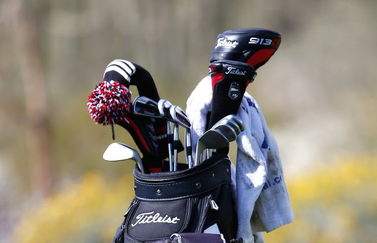 Close-up of different types of golf clubs in a bag