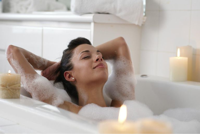 Young woman in bubble bath, smiling