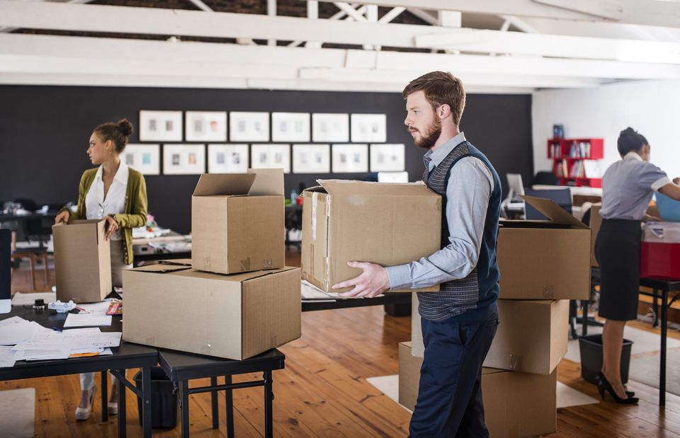 pictures for an office. young man carrying a packed moving box in an office. pictures for office
