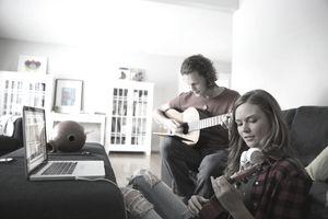 Couple with laptop playing guitar and ukulele