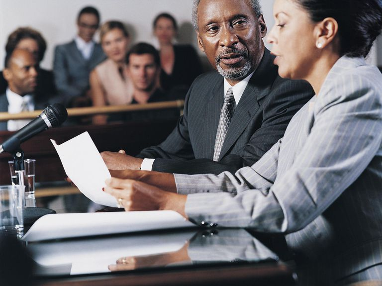 Lawyer Reading a Document and Advising a Man in a Courthouse in Front of a Jury