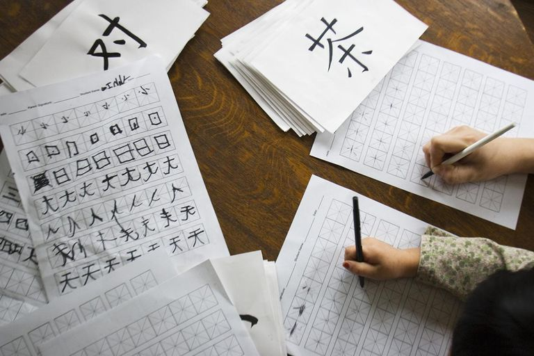 Woman and girl (4-6) studying Mandarin characters