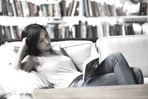 Woman relaxing on sofa reading a book