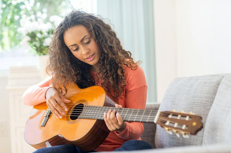 Young woman playing her guitar