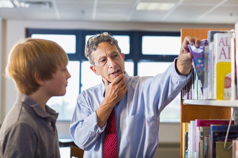 Maestro y profesor trabajando en la biblioteca
