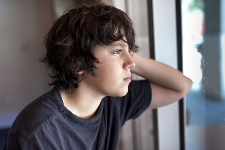 Younger boy looking out a window.