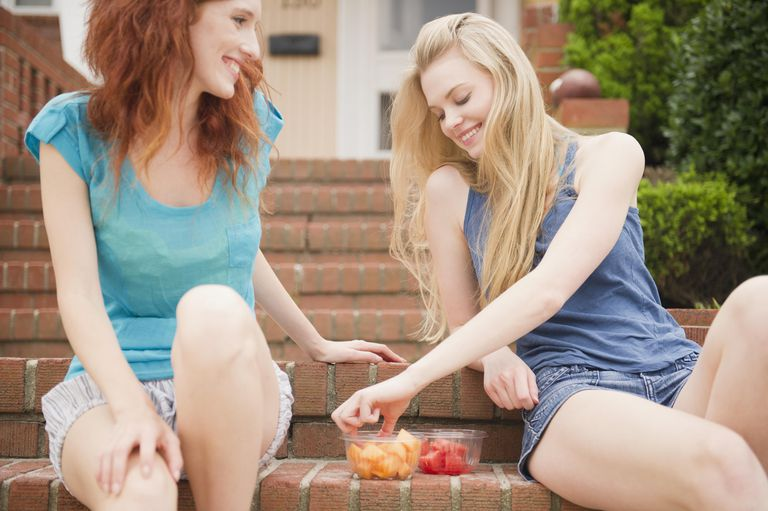Friends eating fruit on front porch