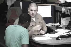 Staff Sgt. Michael Hauck, canvassing recruiter, Recruiting Station Baltimore, goes over an enlistment contract with an applicant.