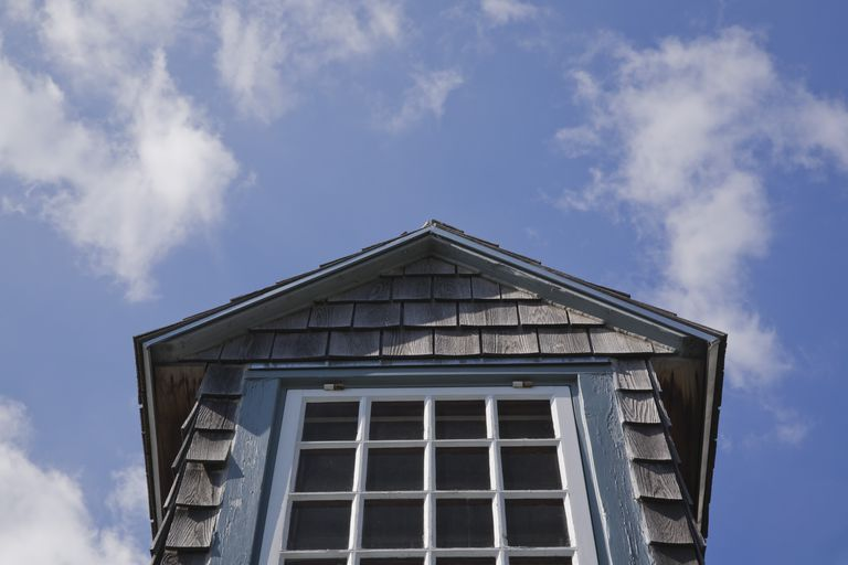 detail low-angle view of a dormer window with gable roof, shingle siding, and 16 glass panes