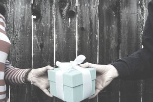 Cropped Image Of Hands Holding Gift Box Against Wooden Fence