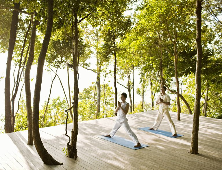 Men doing yoga in a forest
