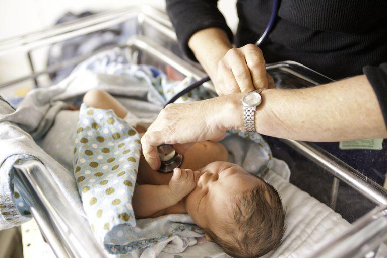 Doctor running tests on newborn baby