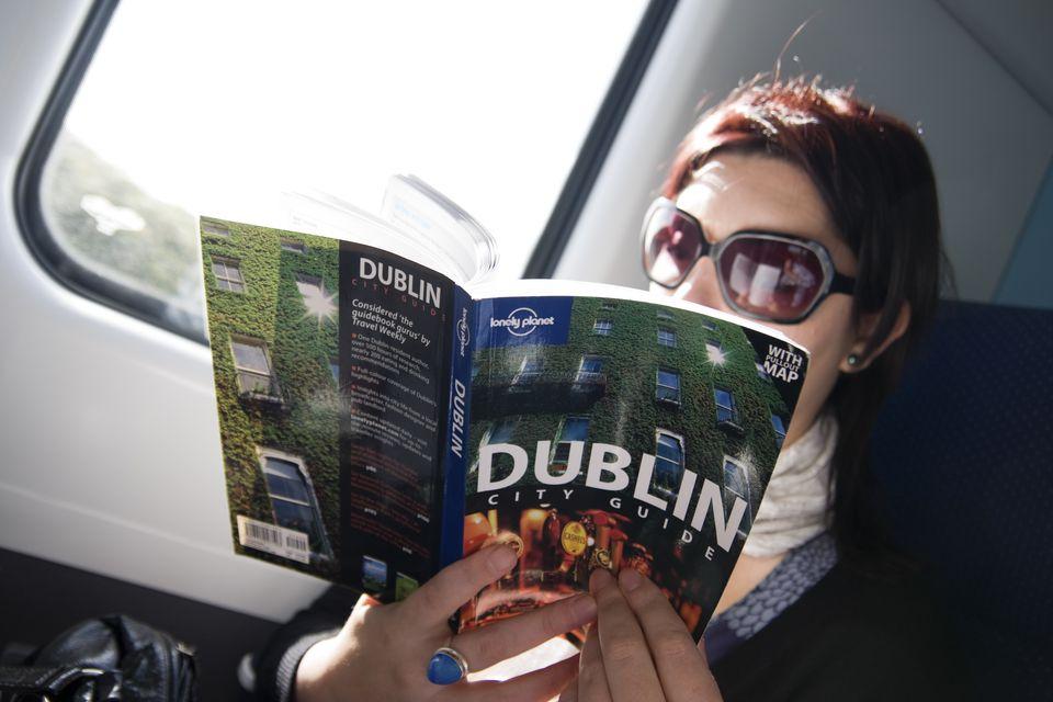 Tourist reading a Dublin City Lonley Planet guidebook