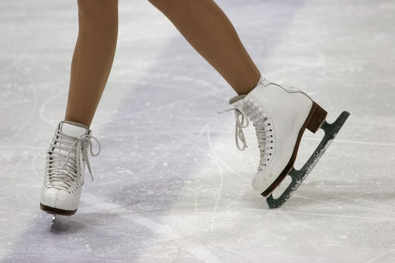 person's legs wearing ice skates on ice