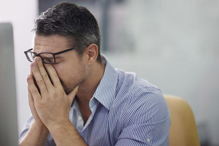 Man sitting at computer rubbing his face