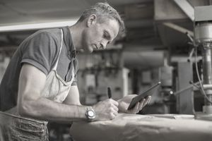 A man in a furniture restoration workshop using a digital tablet, writing on a packet wrapped in brown packaging paper.