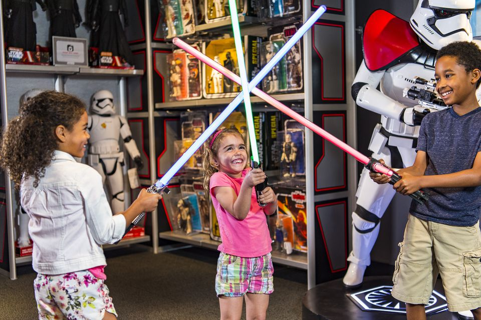 Kids play with light sabers at Disney World