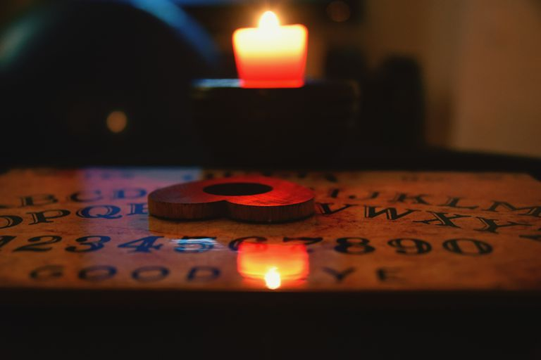 Heart Shaped Planchette On Ouija Board By Candle In Darkroom