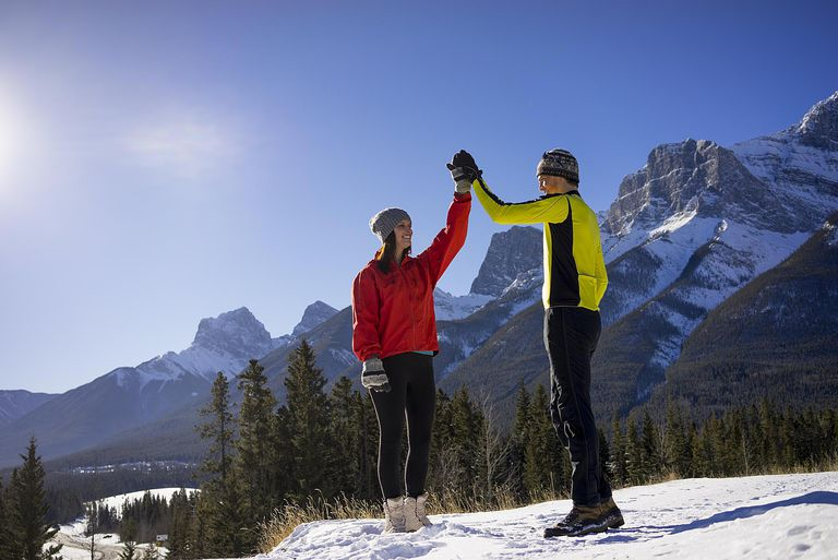 Couple exchanging high-fives on snowy mountainside