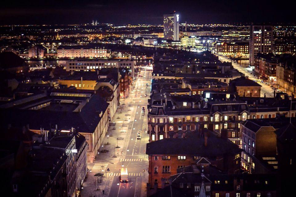 High angle view of road along illuminated buildings at night