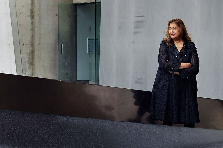 architect Zaha Hadid, long dark hair, arms folded, stanind in front of grey building and shiny sculpture