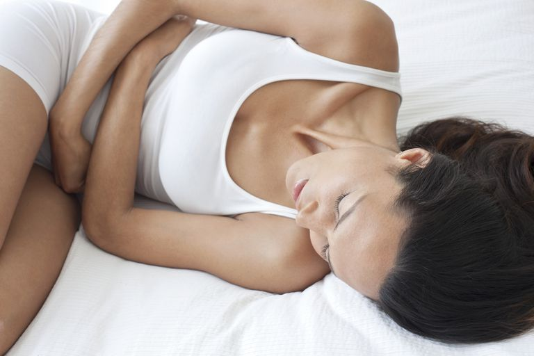 Woman laying on bed holding stomach in pain