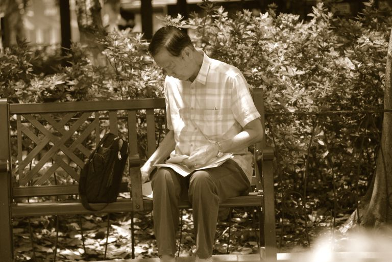 Image shows a sepia tone of a man sitting on a bench in Hong Kong.