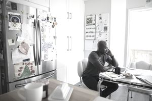 Mature African American man talking on cell phone and working at laptop at kitchen table