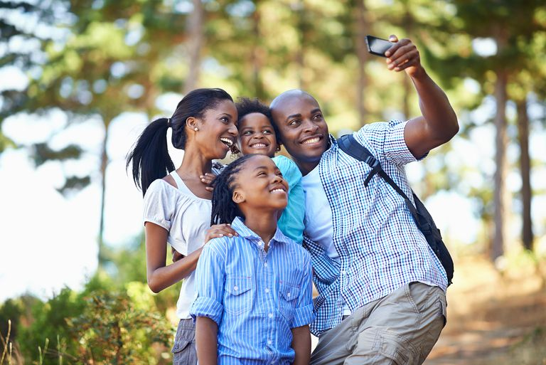 Shot of a happy-looking family taking a self portrait with a camera phone while out hiking in the forest