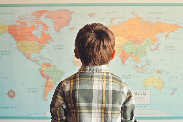 boy looking at a world map poster