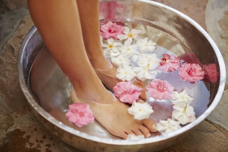 Woman soaking foot in tub full of flowers