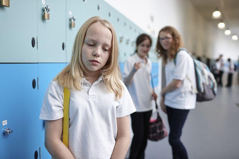girl being picked on near lockers in hallway