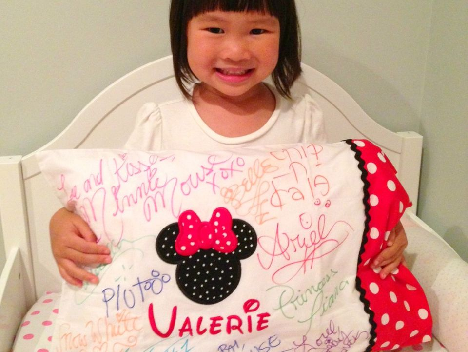 a little girl with a Disney pillowcase