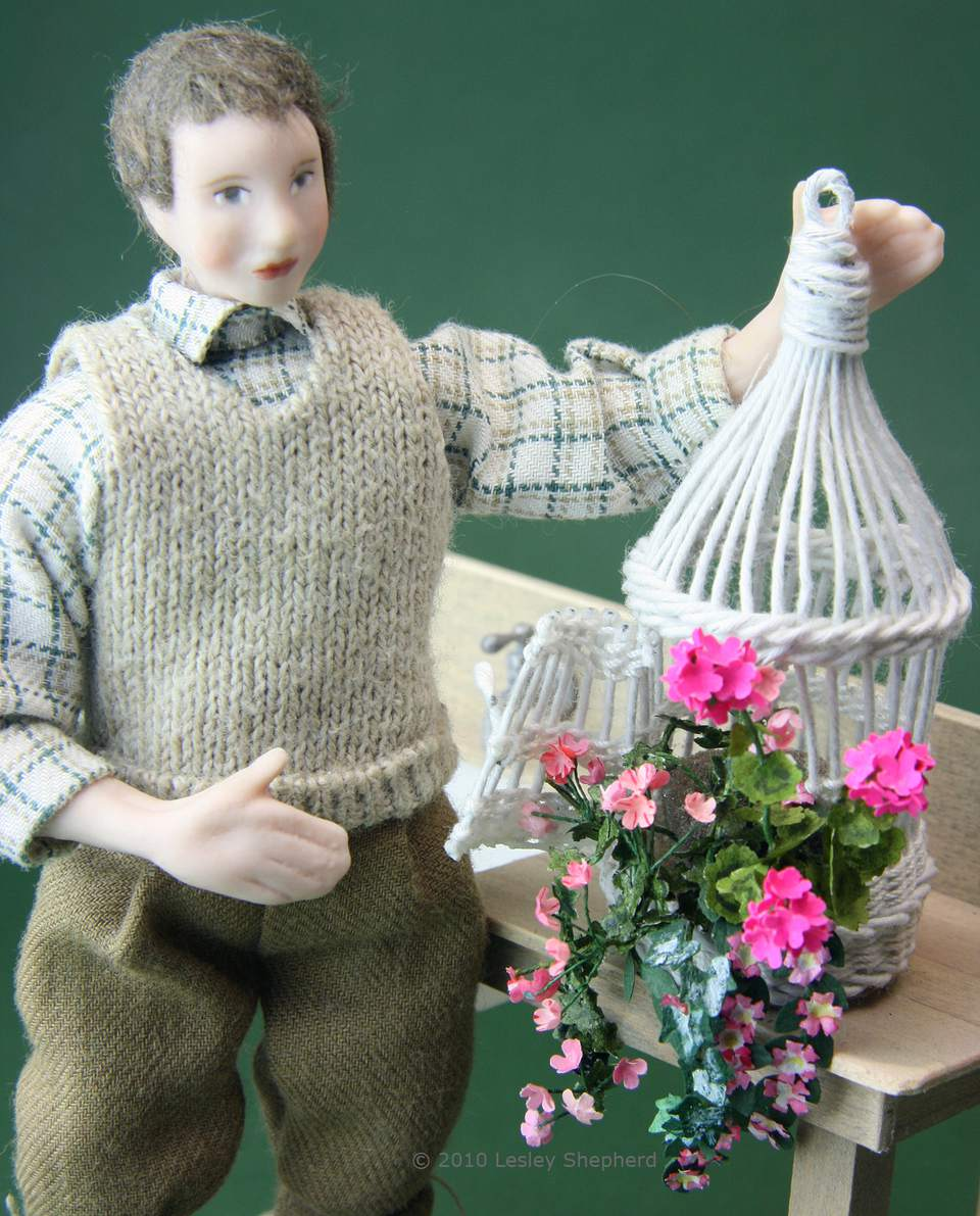 A woven dolls house scale bird cage has been filled with plants for a conservatory.