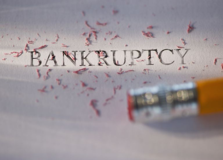 Studio shot of pencil erasing the word bankruptcy from piece of paper