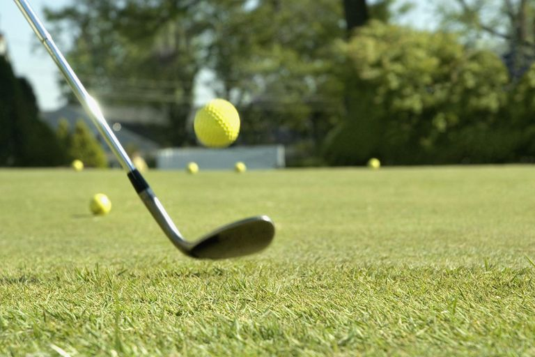 Golf club and ball in mid air, close up