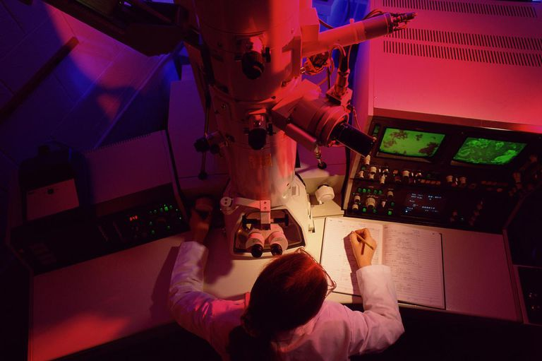 Technician using electron scanning microscope, elevated view